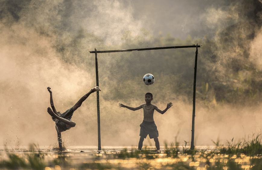two boys playing, football floating in the air, water splashing, green grass